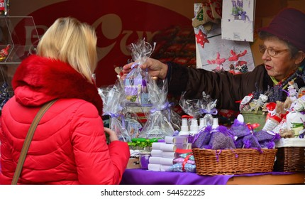 CLUJ-NAPOCA, ROMANIA - DECEMBER 17, 2016: Young blond woman buys cosmetics and beauty products at a stall