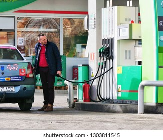 Cluj-Napoca, Romania - February 2, 2019: Man refuels the car tank at the gas station. Taxi driver watches the meter while pumping gas in car tank.