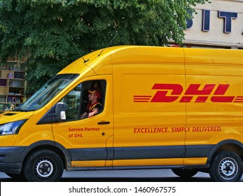 Cluj-Napoca, Romania - July 16, 2019: Yellow DHL van in traffic downtown. DHL Express is an international courier offering worldwide services, being a division of the German logistics company.