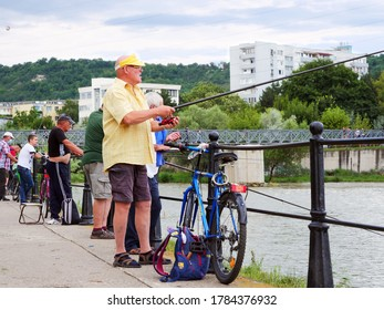 Cluj-Napoca, Romania - July 26, 2020: Anglers with fishing rods fishing at the river on a summer evening. Elderly angler in the foreground holds his rod and spinning reel.