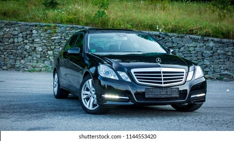 Cluj-Napoca, Romania -July 27, 2018 :2012 model year Mercedes-Benz E250 4MATIC photo session in a parking lot-black metallic paint. Front right view. Isolated car-luxury german design, limousine.