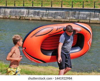 Cluj-Napoca, Romania - July 3, 2019: Two young boys walk upwards the river, one carries an inflatable raft. The boys are going river rafting on a hot summer day.