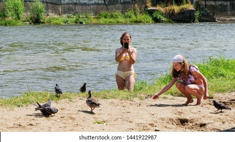 Cluj-Napoca, Romania - July 3, 2019: Young girl in bathing suit feeds biscuits to pigeons and ducks on the river shore. Her mother is taking pictures with her phone.