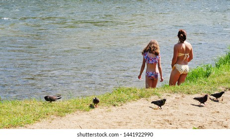 Cluj-Napoca, Romania - July 3, 2019: Mother and daughter in bathing suit enter the river to cool themselves down on a hot summer day.
