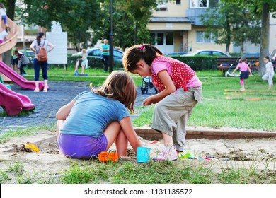 Cluj-Napoca, Romania - July 5, 2018: Two young girls playing in the sandbox at the children's playground