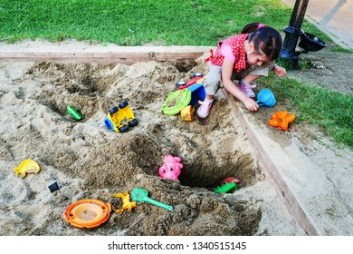 Cluj-Napoca, Romania - July 5, 2018: Little girl plays in the sandbox with plastic toys