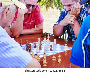 Cluj-Napoca, Romania - July 6, 2018: Happy senior retired men play chess at a table outdoors