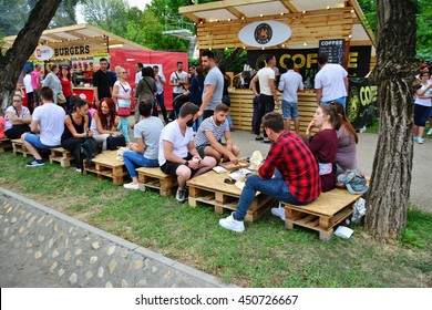CLUJ-NAPOCA, ROMANIA - JULY 9, 2016: People have a snack at the Street Food Festival in central park Cluj. Vendors in stalls sell tasty fast food from different cultures.
