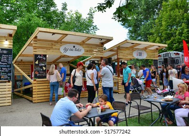 CLUJ-NAPOCA, ROMANIA - JULY 9, 2016: People have a snack in central park Cluj. Vendors in stalls sell tasty fast food from different cultures.