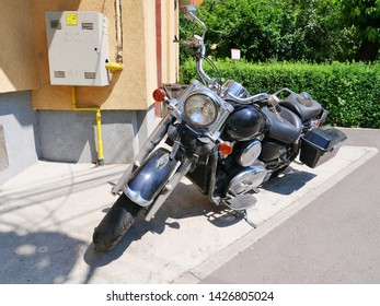 Cluj-Napoca, Romania - June 17, 2019: Kawasaki Vulcan 900 Classic motorbike with tank mounted dashboard, analogue speedometer and warning lights, floorboards, forward controls and panniers. Front view