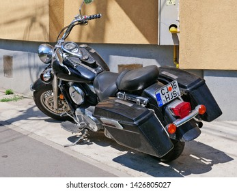 Cluj-Napoca, Romania - June 17, 2019: Kawasaki Vulcan 900 Classic motorbike with tank mounted dashboard, analogue speedometer and warning lights, floorboards, forward controls and panniers. Rear view