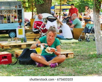 CLUJ-NAPOCA ROMANIA - JUNE 9 2017: Young woman eats fast food sitting crossed legs in the grass being surrounded by people relaxing in the park