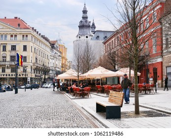 Cluj-Napoca, Romania - March 30, 2018: Tourists relax at outdoor terraces on the Union square promenade surrounded by beautiful old buildings in the center of the town.
