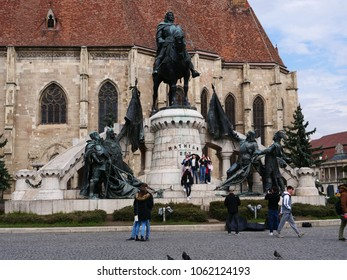 Cluj-Napoca, Romania - March 30, 2018: Young tourist girls climb the Matthias Corvinus Monument posing for the camera. The monument and the St. Michael's Church in the background are the town's symbol