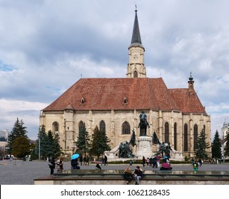 Cluj-Napoca, Romania - March 30, 2018: 15th century St Michael's Church with the Matthias Corvinus monument in front is the symbol of the town and a great tourist attraction.