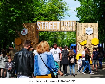 Cluj-Napoca, Romania - May 12, 2019: People flock to the street food festival in central park Cluj. Decorated wooden gate welcomes the crowd to taste goodies cooked by famous chefs.