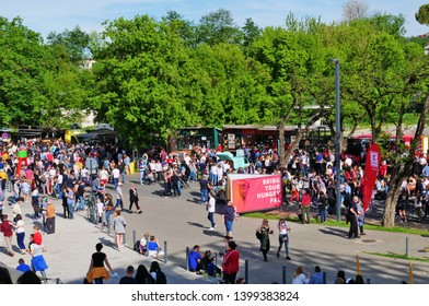 Cluj-Napoca, Romania - May 12, 2019: Many people eat and drink at the street food festival. People stay in line to buy fast food at food trucks.