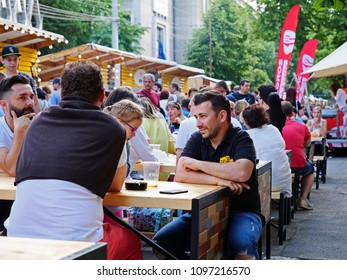 Cluj-Napoca, Romania - May 19, 2018: Friends and families eat out and have a drink at street food stalls on a summer evening