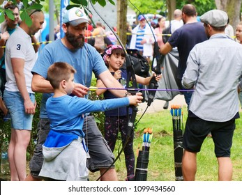 Cluj-Napoca, Romania - May 19, 2018: Experienced archers teach children archery in the park.