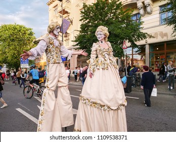 Cluj-Napoca, Romania - May 19, 2018: Stilt walker street performer couple dressed in medieval costumes meet and greet the people on the street