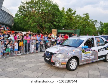 Cluj-Napoca, Romania - May 5, 2018: Dacia Logan race car checks in at the finish line at the Transylvania Rally late in the evening. People admire the pilot and copilot.