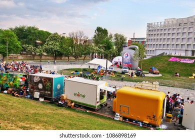 Cluj-Napoca, Romania - May 5, 2018: Food truck caravan serves junk food to the crowd gathered in the park. People standing in line for a snack.