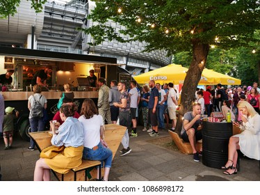 Cluj-Napoca, Romania - May 5, 2018: People stay in line to buy fast food at food trucks in the evening. People eat junk food at tables.