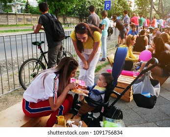 Cluj-Napoca, Romania - May 5, 2018: Young mother teaches baby in stroller to color a children's book. People eat fast food at tables in the background.