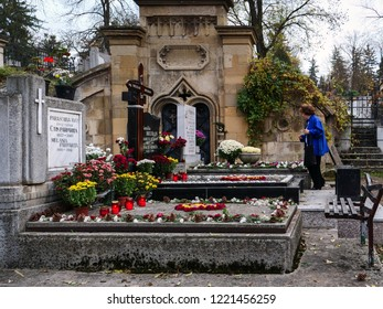 Cluj-Napoca, Romania - November 1, 2018: Senior woman stands at a grave paying respect to deceased relatives with flowers and lighting candles on All Souls' Day