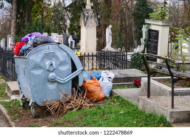 Cluj-Napoca, Romania - November 1, 2018: Overflowing metal garbage container.  Mobile dumpster with four wheels in the cemetery.