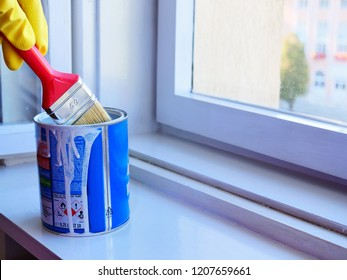 Cluj-Napoca, Romania - November 10, 2018: Hand in yellow rubber gloves dips a paintbrush in paint can to load it with white paint. Window frame restoration in home interior,