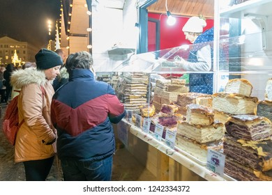 CLUJ-NAPOCA, ROMANIA - NOVEMBER 23, 2018: People waiting for a piece of pie at the Christmas market in the Unirii Square, Transylvania, Romania