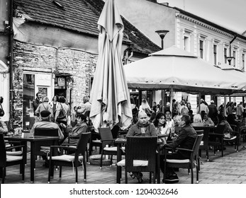 Cluj-Napoca, Romania - October 14, 2018: People sit at tables and drink at an outdoor terrace of a pub in front of an old building in the evening.