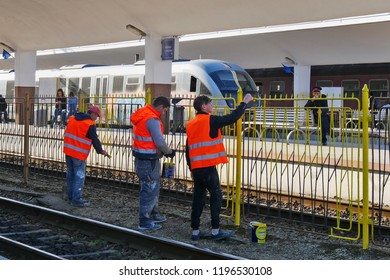 Cluj-Napoca, Romania - October 4, 2018: Workers paint with brushes and yellow paint the iron fence of the railway station perimeter. A station agent in uniform is watching them.