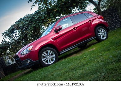 Cluj-Napoca, Romania -September 16, 2018 :2012 model year Mitshubishi ASX 4WD photo session in a private yard-red metallic paint. big panoramic sunroof. Isolated car-luxury design, SUV.