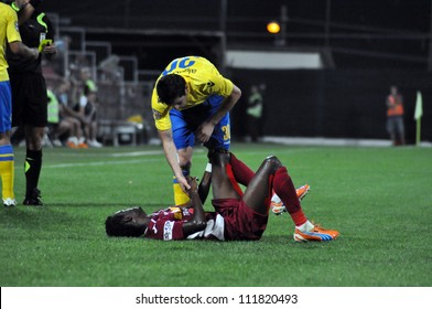 CLUJ-NAPOCA, ROMANIA - SEPTEMBER 2: Fair play of M. Laurentiu (yellow) after a  fault against M. Sougou (red) during a match between CFR Cluj - P. Ploiesti, final score 2-2, Sept 2, 2012 in Cluj, RO