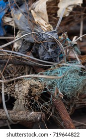 A clump of turquoise plastic fibres and other refuse materials intertwined with rusting steel cabling (portrait orientation).