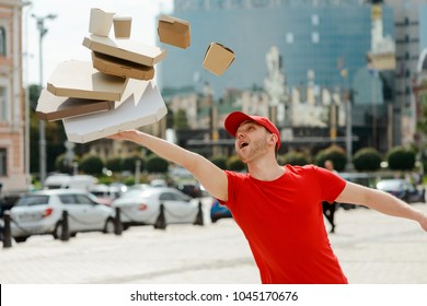 Clumsy delivery man stumbled and dropped boxes with pizza, wok noodles and cup of coffee. Fail, awkward situation at work.