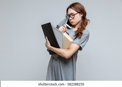 Clumsy Female nerd in eyeglasses which talking on phone and holding laptop, clipboard and notebook