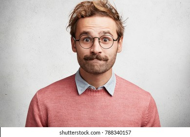 Clumsy male geek presses lips, looks in bewilderment, feels embarrassed in presence of beautiful woman, wears round big spectacles, isolated over white concrete background. Excited emotional male
