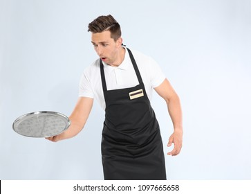 Clumsy waiter dropping empty tray on light background