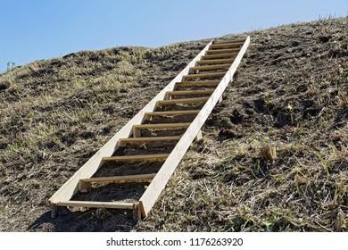 A clumsy wooden ladder lying on an earthen hill. Conceptual - movement up steep inconvenient steps: business, creativity, human development