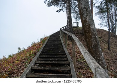 A clumsy wooden ladder lying on an earthen hill. Conceptual - movement up steep inconvenient steps: business, creativity, human development