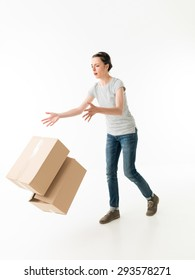 clumsy young woman dropping moving boxes and tripping. on white background
