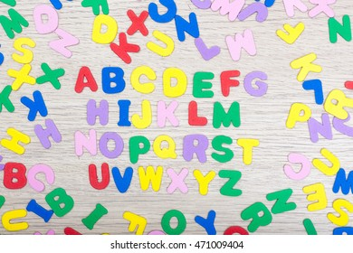 A cluster of colored letters on wooden table with the alphabet in the middle. studioshot.