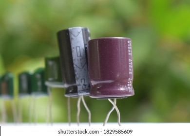 cluster of electric capacitors in blurred background - electronic evolution , electric evolution , capacitor evolution , electronic queue - uF capacitor uf condenser