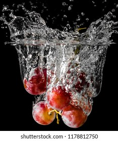 A cluster of grapes dopped into liquid creating beautiful splash