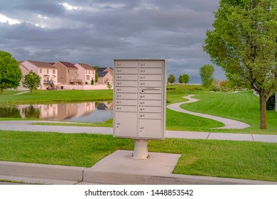 Cluster mailbox against pond and houses under sky with thick gray clouds