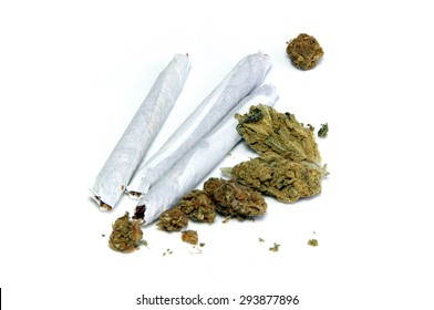 A cluster of marijuana buds and three joints up close over white.