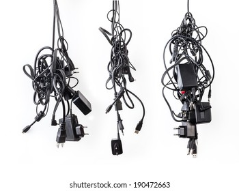 Cluster of messy chaotic power cables and adapters isolated on white background